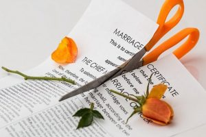 scissors cutting a marriage certificate