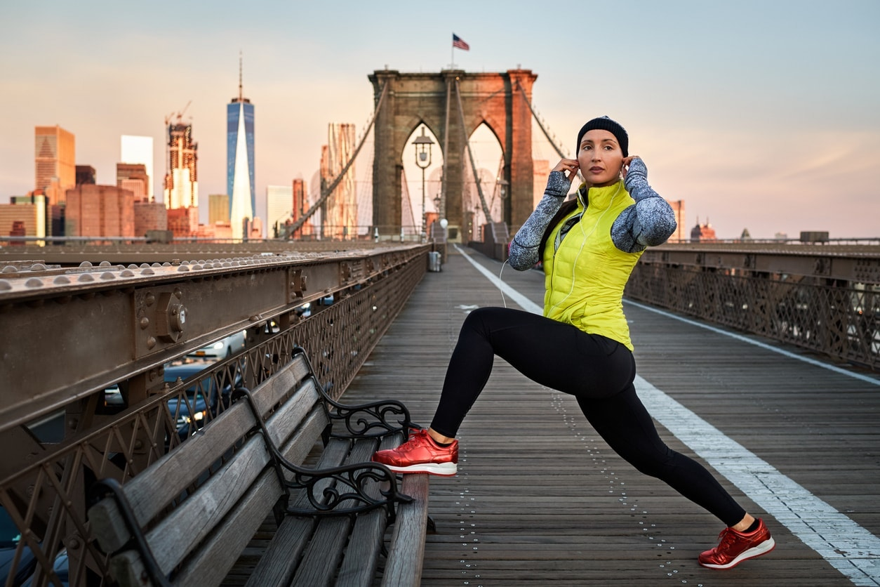 Female athlete stretching on Brooklyn bridge