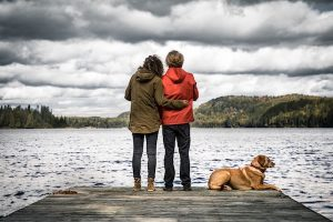 couple at lake dock with dog