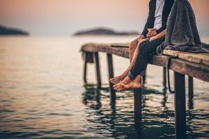 couple sitting on dock with feet dangling over water