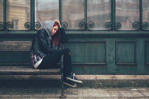 depressed teenage girl sitting on urban-bench